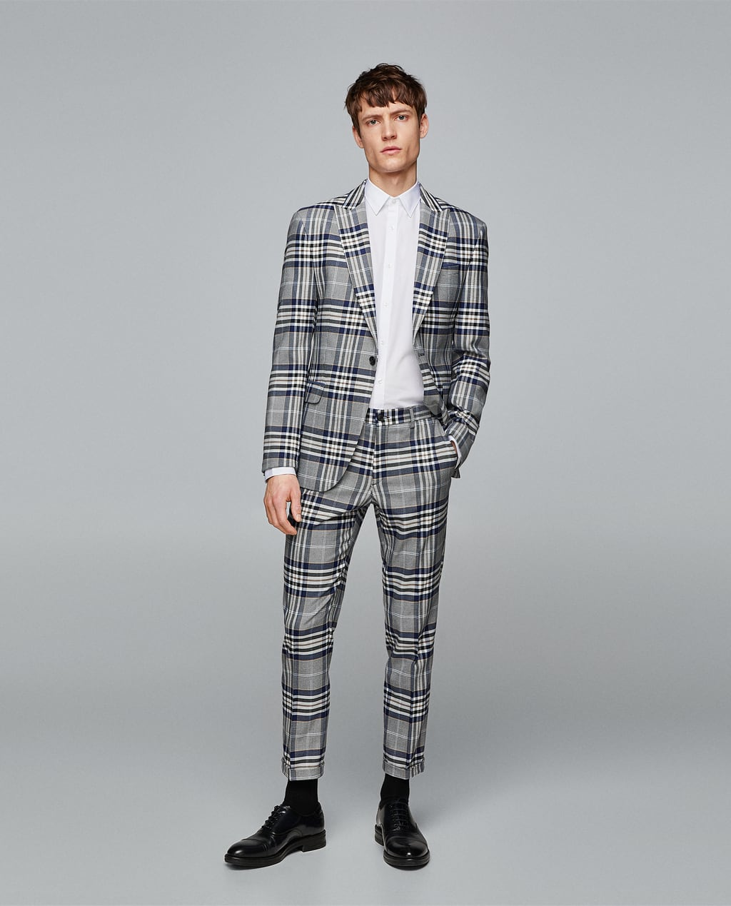 Checked blazer with peak lapels and long sleeves. Features two front flap pockets, one besom pocket at the chest with contrasting pocket square and lining with an inside pocket. Double back vents, buttoned cuffs and button fastening in the front.