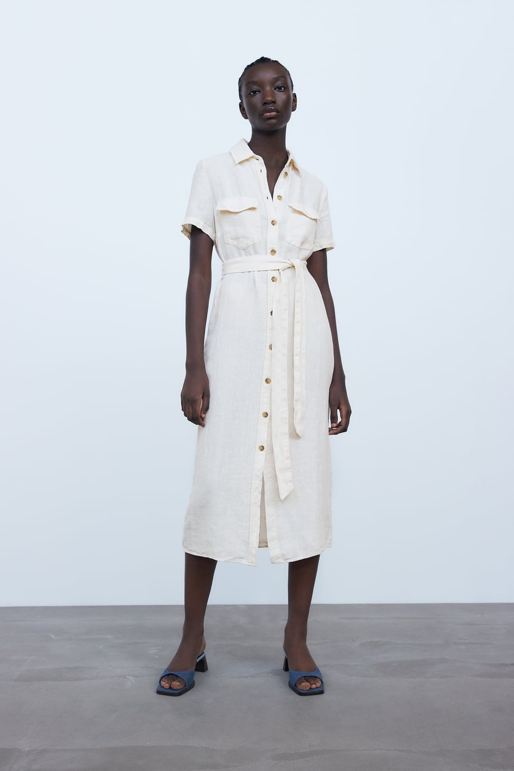 Linen dress. Lapel collar and short sleeves. Front patch pockets. Tied self belt. Front closure with contrasting buttons.